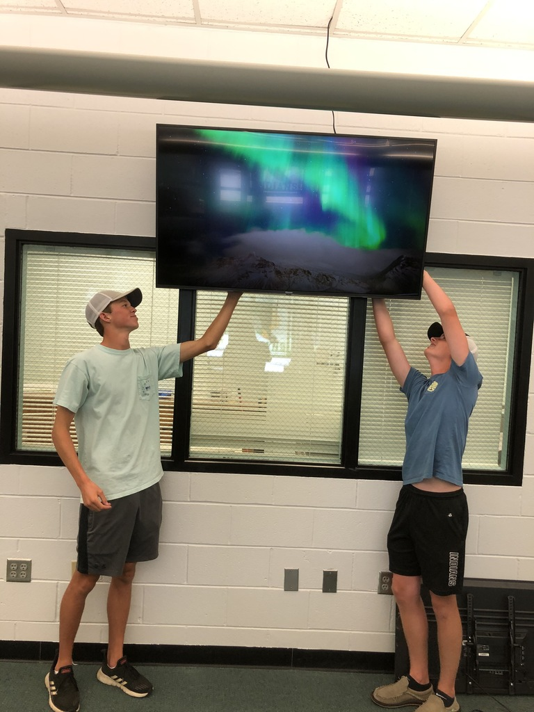 Students helping with TV installation..